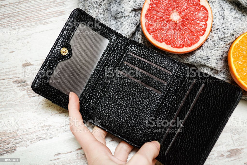 Little black purse in female hand and citrus on a sweater. Fashionable concept. stock photo