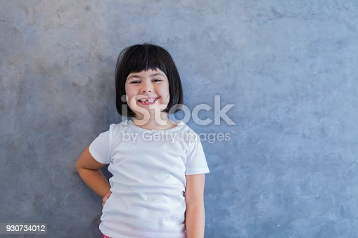 istock Little blackhair girl by wall 930734012