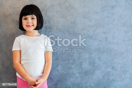 istock Little blackhair girl by wall 937764426
