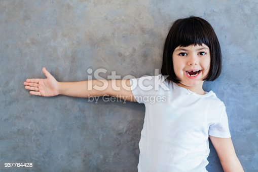 istock Little blackhair girl by wall 937764428