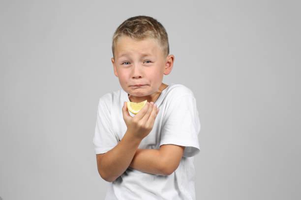 Kleinen, blonden Jungen in eine Zitrone beißt – Foto