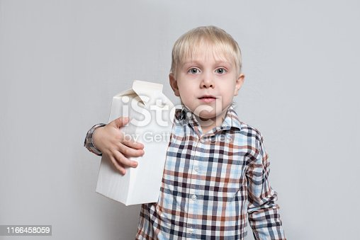 istock little blond boy cuddles a large white carton package. Light background 1166458059