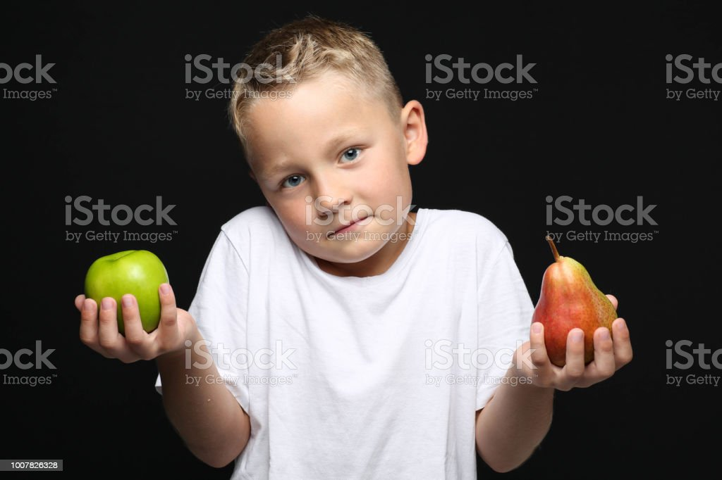 kleine, blonde junge zweifelnd hält einen Apfel und eine Birne in der hand – Foto
