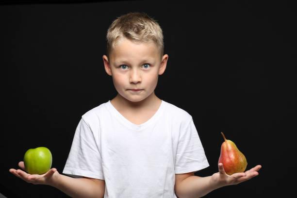 kleine, blonde junge zweifelnd hält einen Apfel und eine Birne – Foto