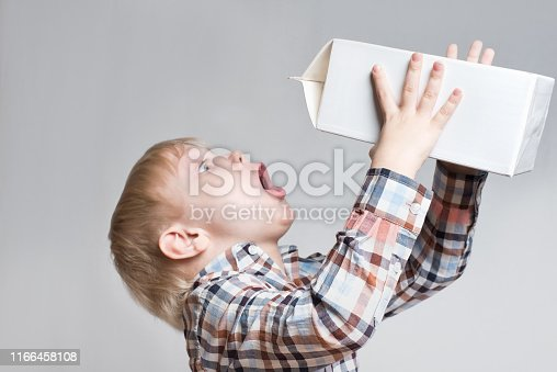 istock Little blond boy drinks from a large white package. Light background 1166458108