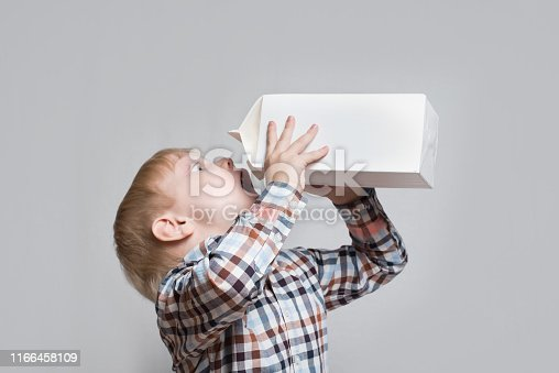 istock Little blond boy drinks from a large white package. Light background 1166458109