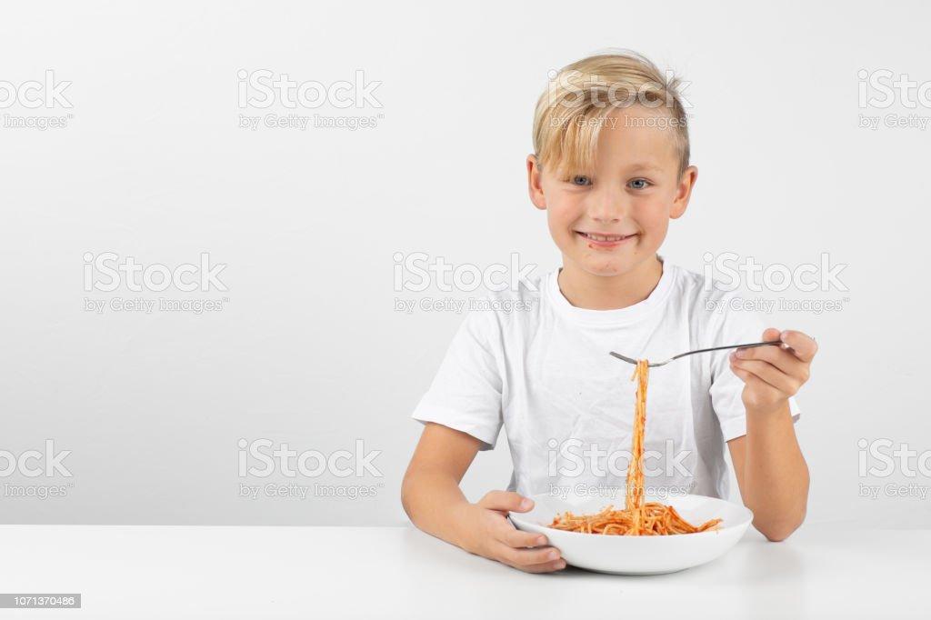 kleine blonde junge isst Spaghetti und lächelt – Foto