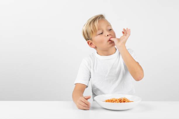 kleine blonde junge isst spaghetti – Foto