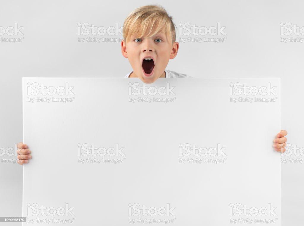 kleine blonde junge hält ein Plakat – Foto