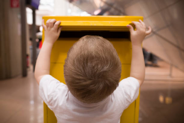 A little blond boy in a white t-shirt puts a letter into a yellow postbox. Sending post to a friend at the post office. A little blond boy in a white t-shirt puts a letter into a yellow postbox. Sending post to a friend at the post office. letterbox format stock pictures, royalty-free photos & images