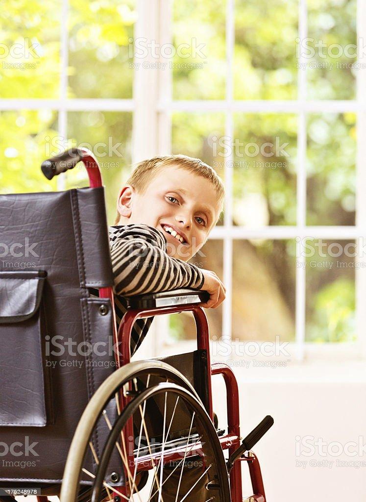 Little blond boy in wheelchair smiles over shoulder stock photo