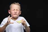 Little, blond boy is eating a piece of a lemon