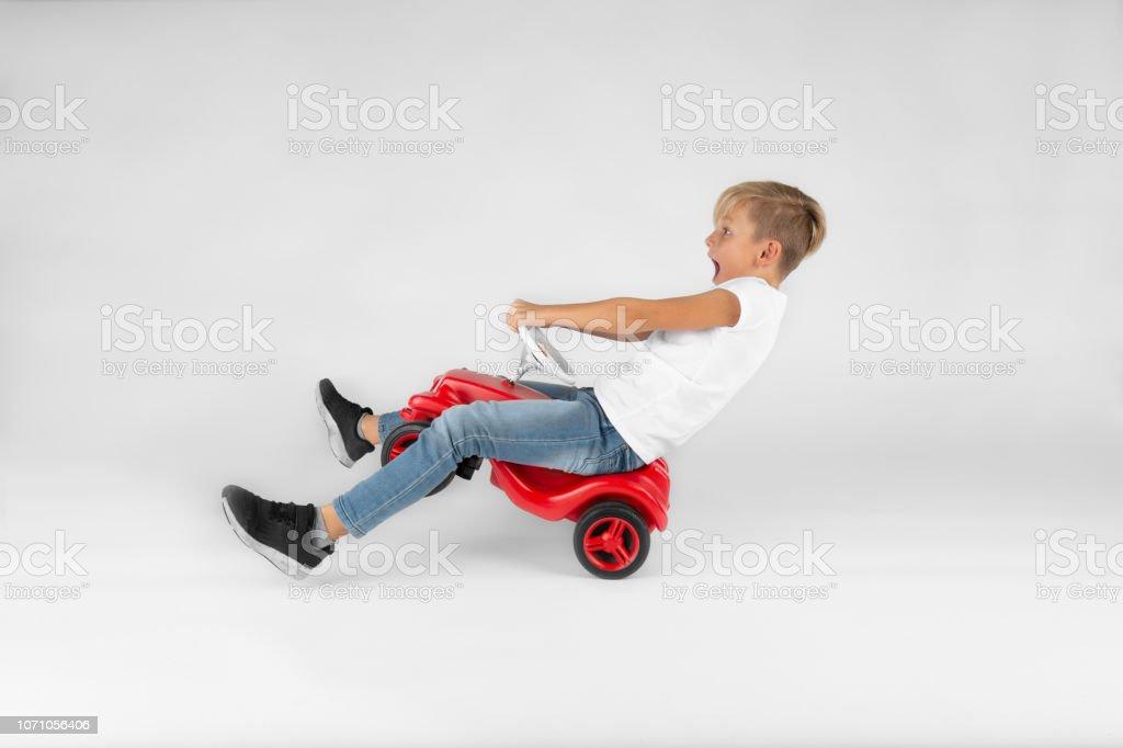 kleine blonde junge reitet ein Modellauto – Foto