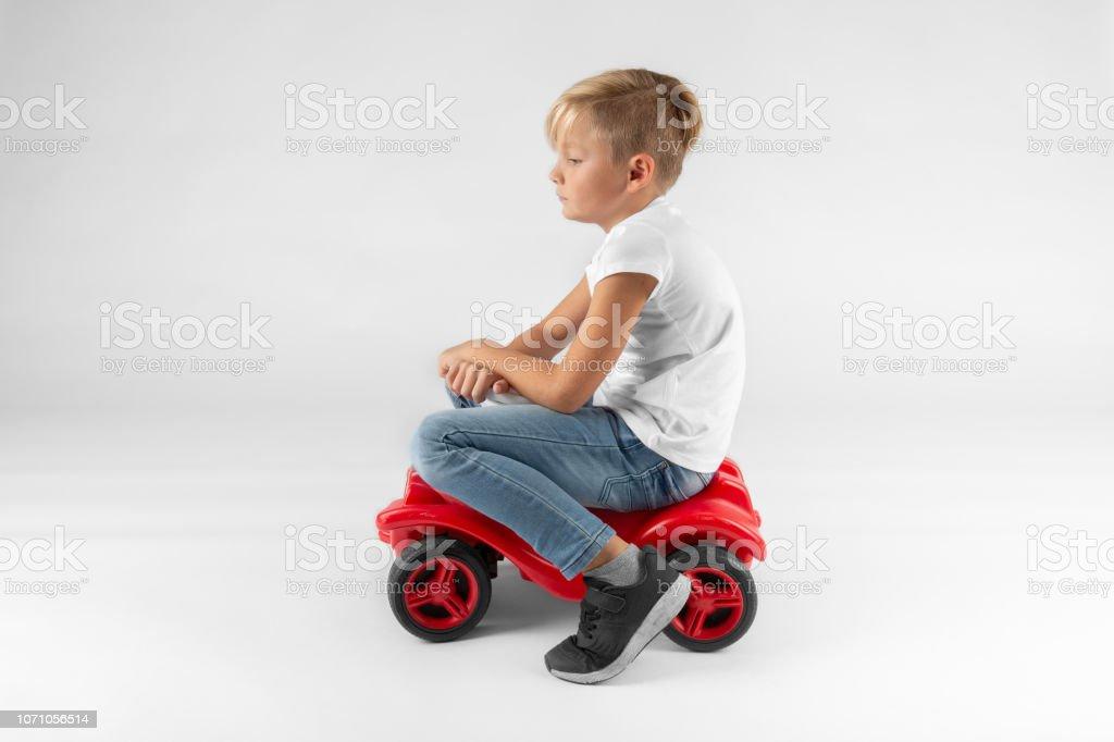 kleine blonde Junge sitzt auf einem Modellauto – Foto