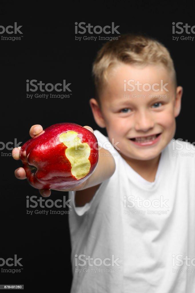kleinen blonden Jungen lächelt und hält einen roten Apfel – Foto