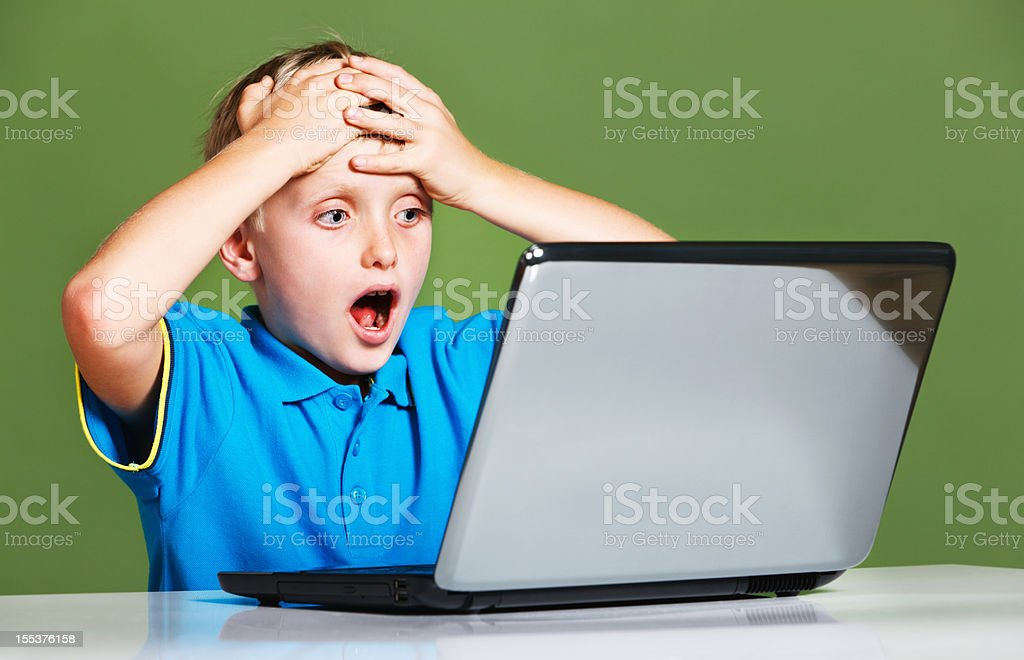 Little blond boy looks at laptop screen amazed or shocked stock photo