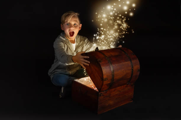 kleinen blonden Jungen öffnet eine Truhe – Foto
