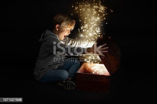 little blond boy opens a chest anxiously, light inside, glitter bright