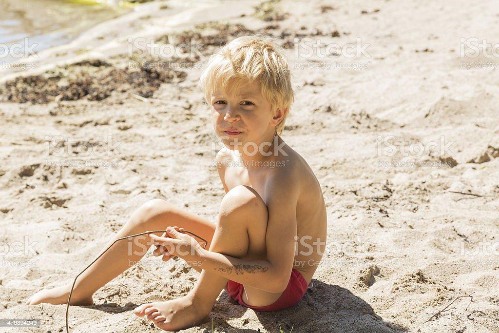 Little blond boy sitting on the beach. royalty-free stock photo
