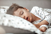 istock Little blond boy sleeping in his bed. 1223560129