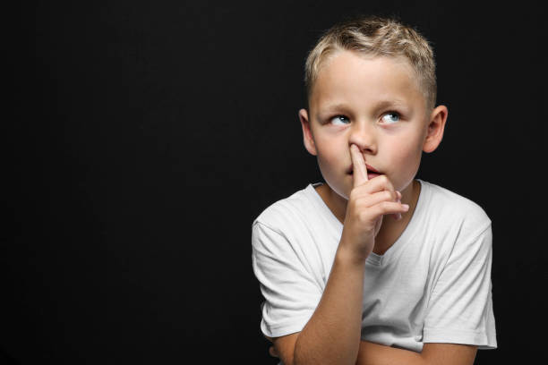 little blond boy thinks and drills with finger in the nose stock photo