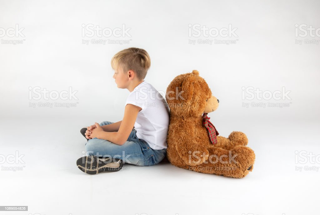 little blond boy is sitting back to back on the floor with a big...