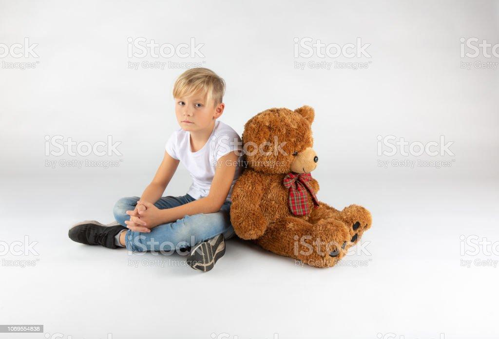 little blond boy is sitting sadly on the floor with a big teddy bear