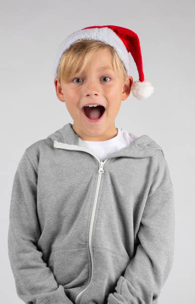 kleinen blonden Jungen mit einer Weihnachtsmütze ist überrascht – Foto