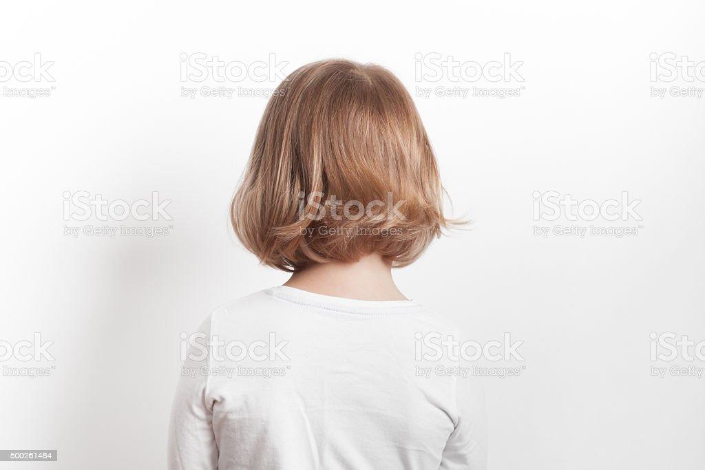 Little blond Caucasian girl back over white background stock photo