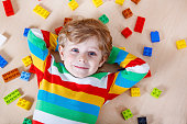 Little blond child playing with lots of colorful plastic blocks
