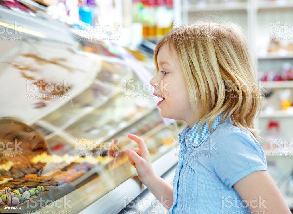 little blond girl choosing chocolate stock photo