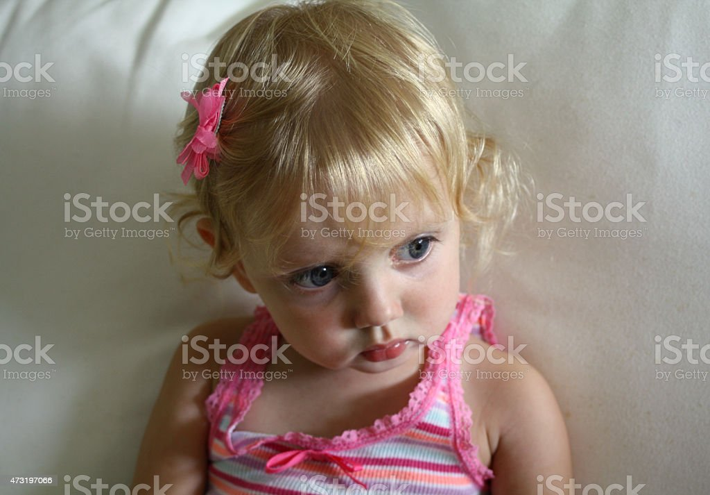 Little Blond Girl in Contemplation Sitting on a Sofa stock photo