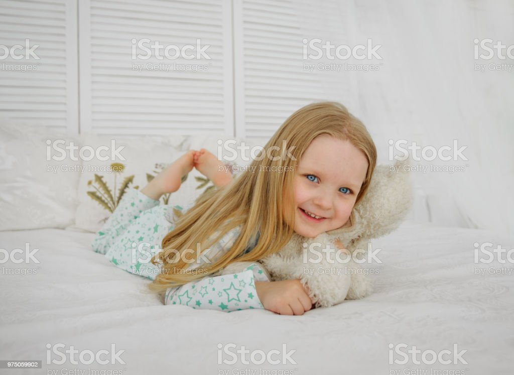 A little blond girl lies in bed and hugs a bear. Girl in pajamas,...