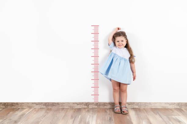 little blond girl measuring height on white wall. - bassino foto e immagini stock