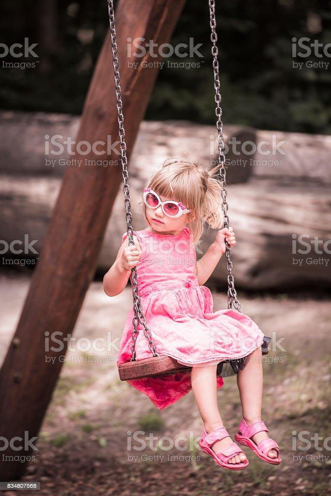 Little blond girl on a swing stock photo