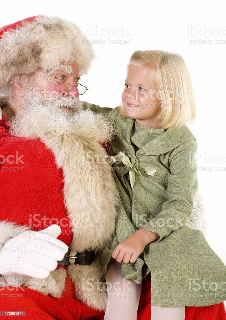 Little blond girl on Santa's lap smiles at him royalty-free stock photo