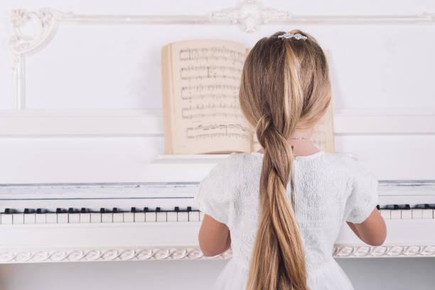 küçük sarışın kız beyaz elbiseli beyaz piyano oynamak - beyaz elbise stok fotoğraflar ve resimler