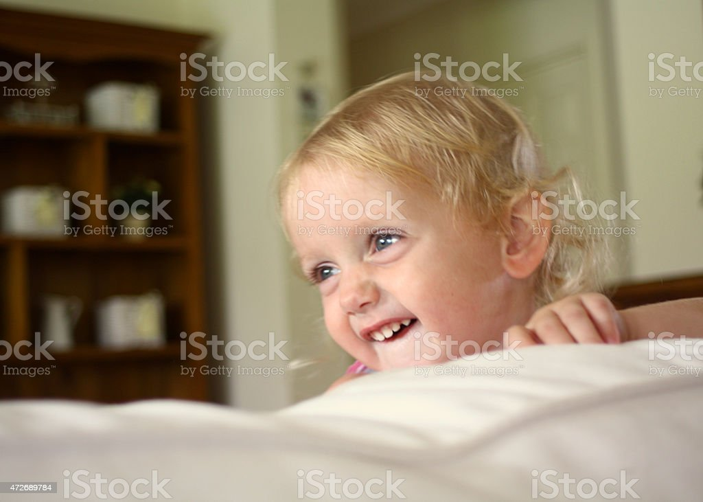 Little Blond Girl Playing and Laughing on the Sofa stock photo