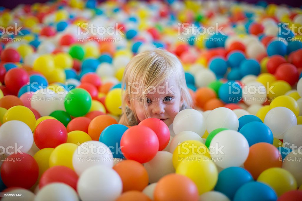 Little blond girl plays in a ball pool stock photo