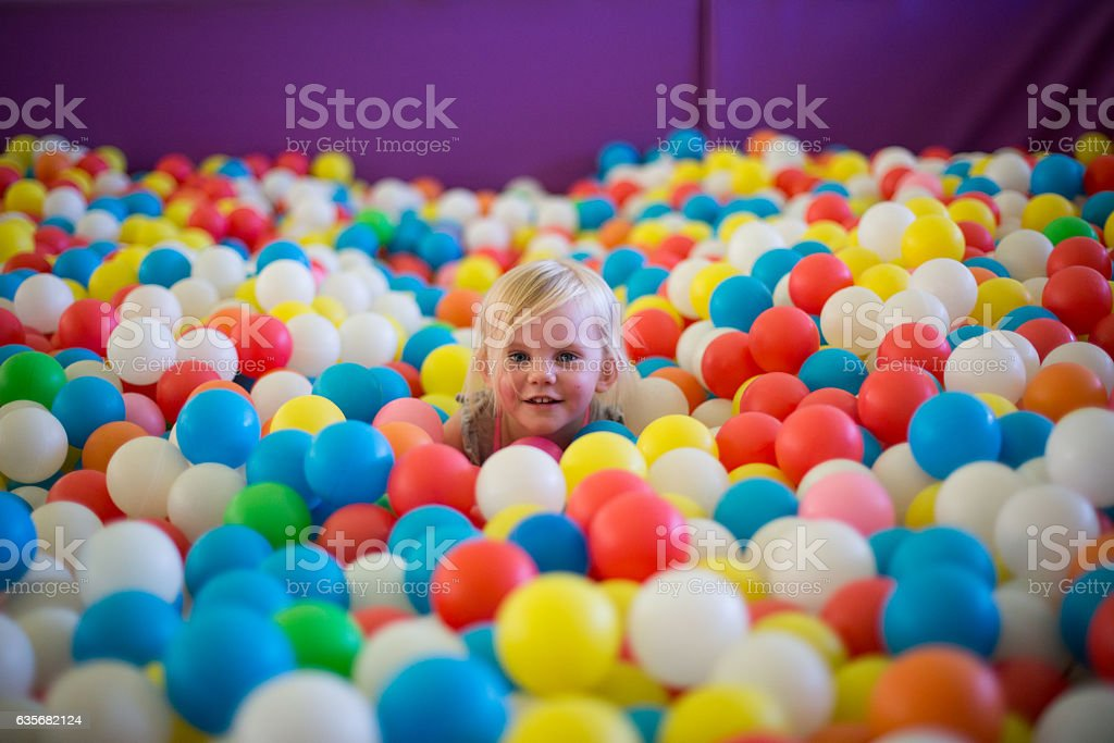 Little blond girl plays in a colorful ball pool - foto de acervo