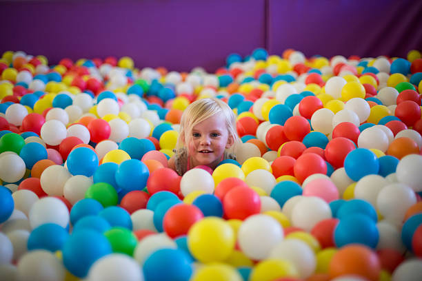 Little blond girl plays in a colorful ball pool stock photo