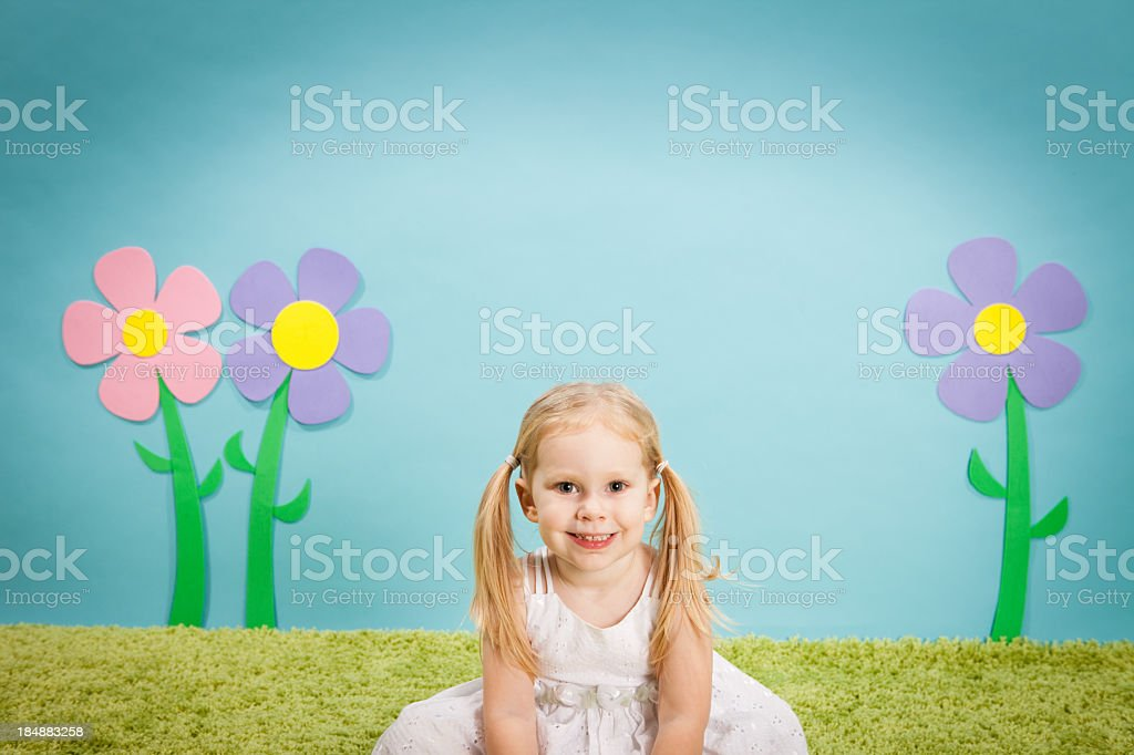 Little Blond Girl Sitting and Smiling in Whimsical Outdoor World stock photo