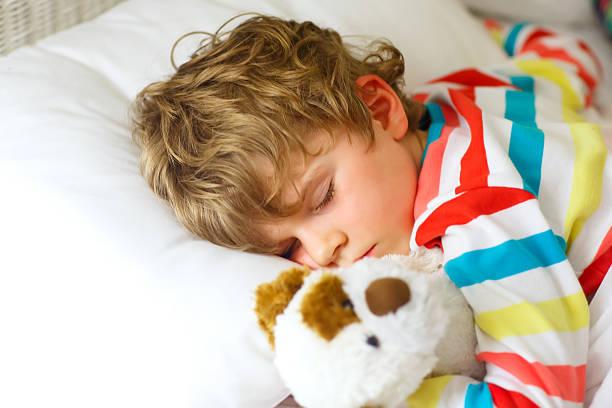 little blond kid boy in colorful nightwear clothes sleeping - bett für jungs stock-fotos und bilder