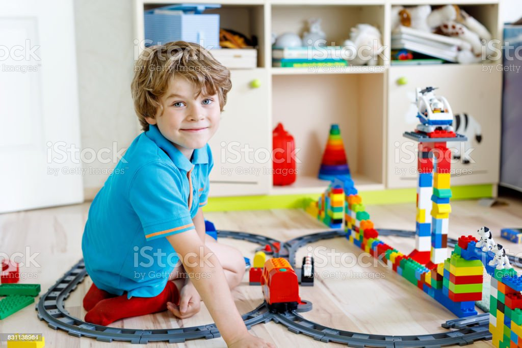 little blond kid boy playing with colorful plastic blocks and creating train station stock photo