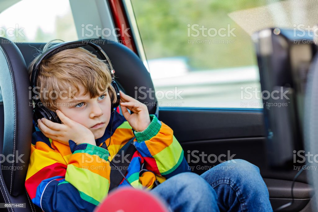 Little blond kid boy watching tv or dvd with headphones during long car drive stock photo