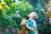 Little blond preschool kid boy discovering flowers, plants and butterflies at botanic garden. Schoolchild interested in biology. Active educational leisure with preschool kids in museum.