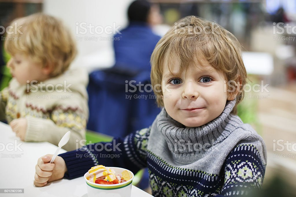 Little blond toddler boy eating ice cream iin shopping mall royalty-free stock photo