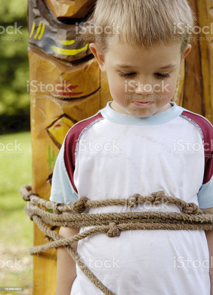 Little blonde boy is tied up at a totem pole royalty-free stock photo