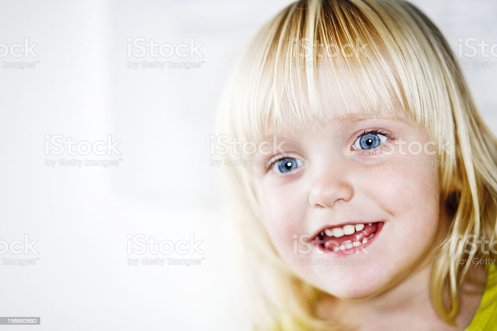 Little blonde charmer smiles in delight stock photo