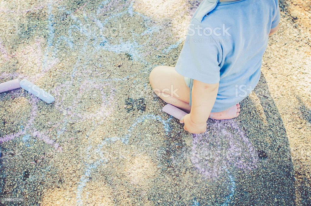Little blonde child playing with colorful chalk on the floor photo libre de droits